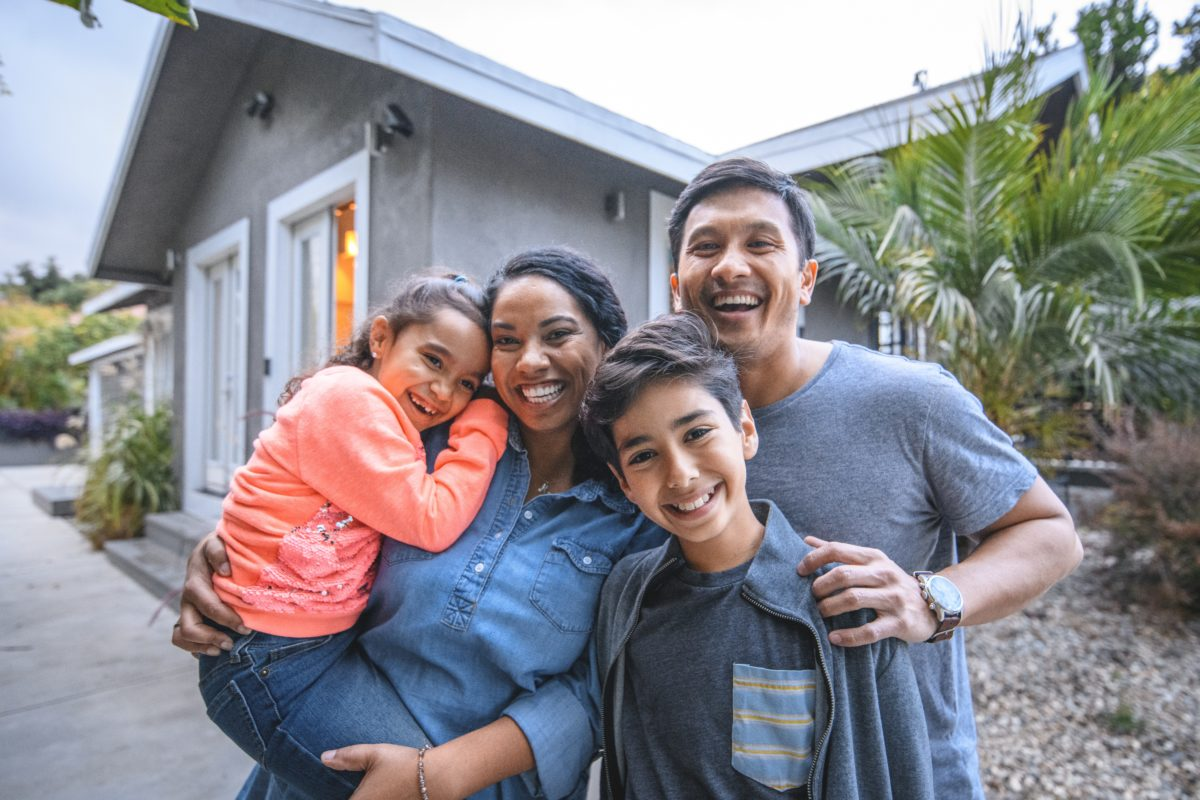 Family Standing in front of their home smiling